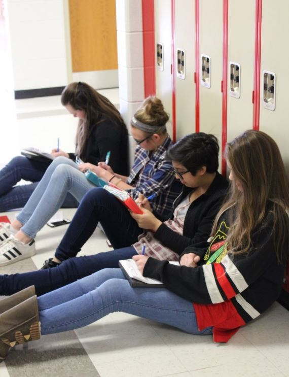 Students reading in the hall outside of their lockers