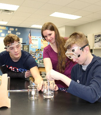 Female science teacher assisting two male students with an experiment